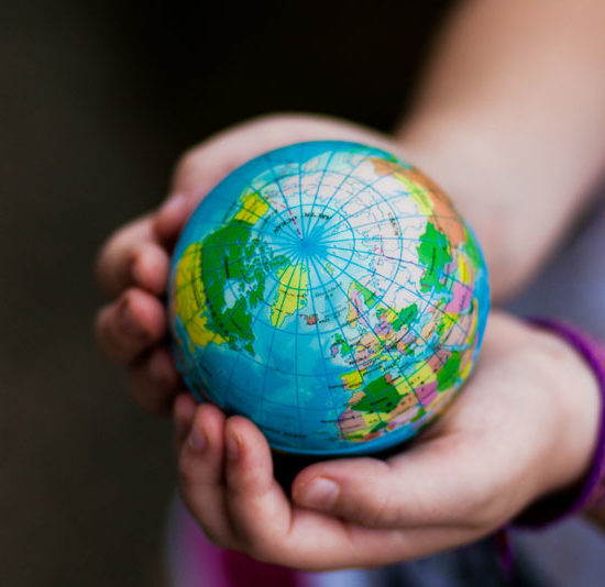 girl holding a globe in her hands Easy Ways Your Business Can Go Green for Earth Day