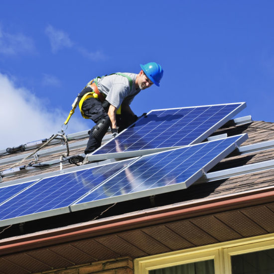 Considering Solar Panels? Here's What You Should Know About Insurance man installing solar panels on the roof of a house