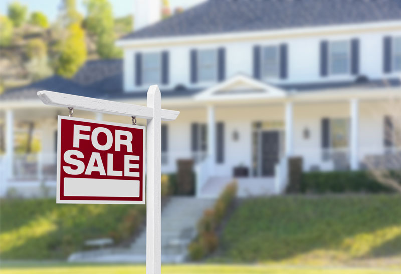 Insurance Factors to Consider When Buying a New Home house for sale with sign outside