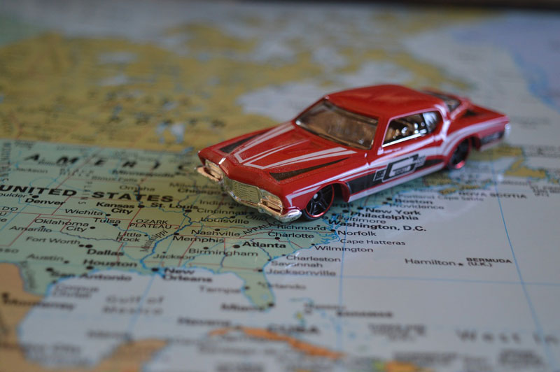 How to Prepare Your Vehicle for a Summer Road Tripa red toy car on an atlas