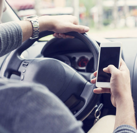 a person driving while texting on their phone