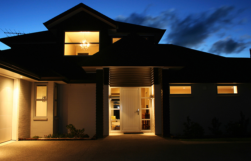 a home's exterior lights on at dusk