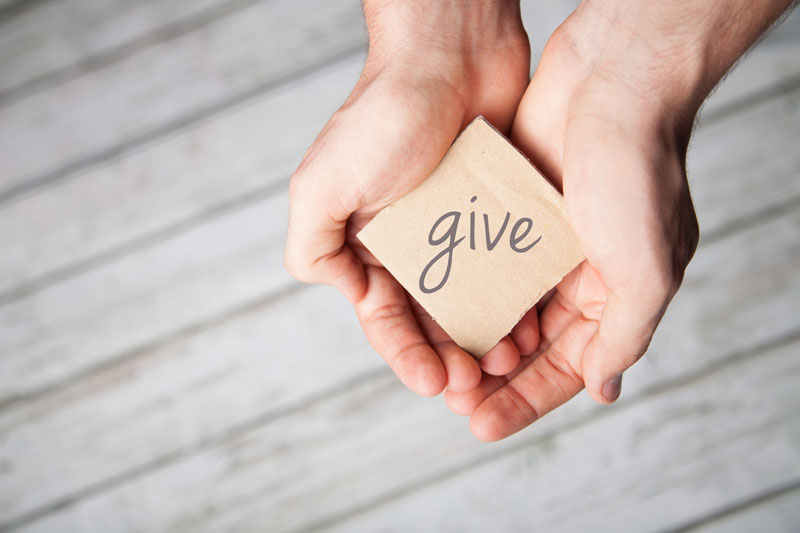 hands holding out a sign saying 'give'