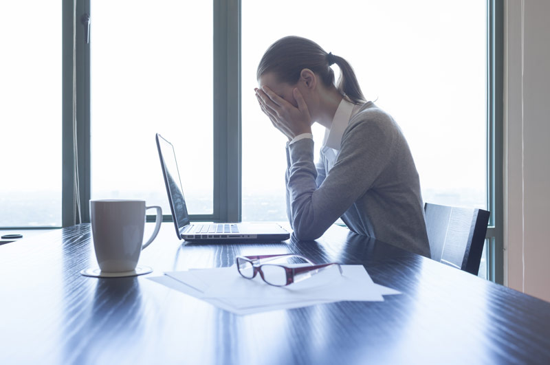 a woman stressed out at a laptop